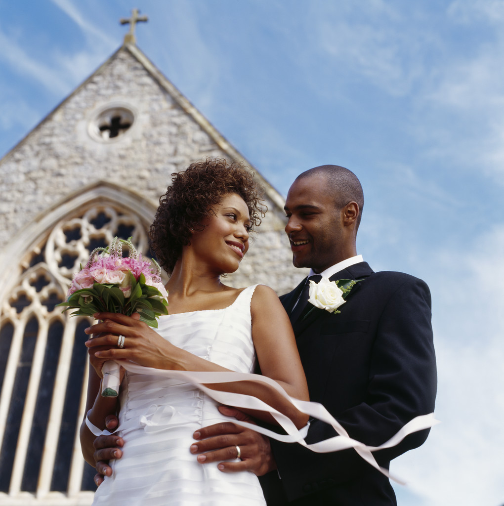 low angle view of a newlywed couple standing together outside a church